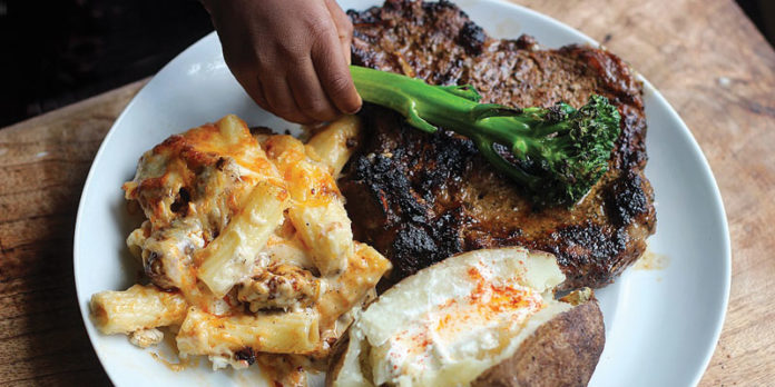 Steak, Baked Mac-n-Cheese, and Baked Potato with Brussels Sprout Garnish.