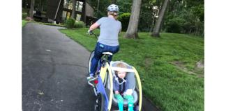 Courtney Stinson pulls Ellie in an adapted bike trailer.