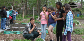 Students from Mitchell Elementary smell fresh herbs in the garden with their teacher Mr. Popkey