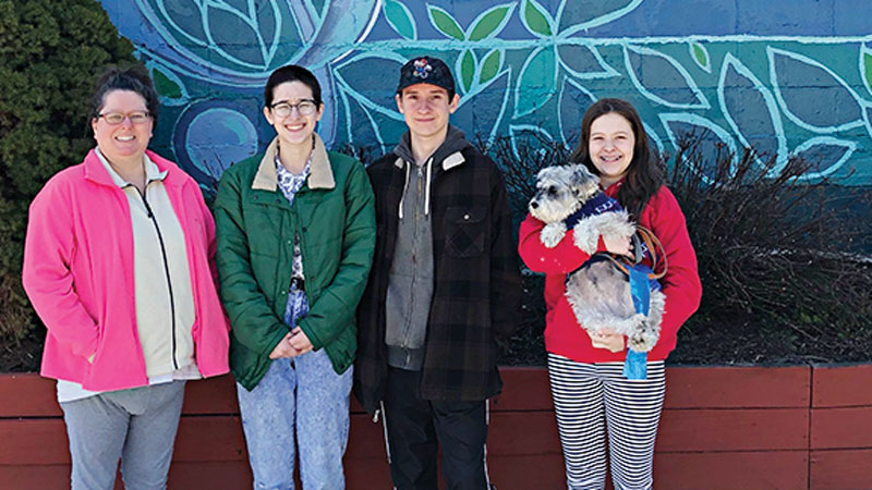 Melodee Bourdeau, Emma, Roger, and Sophie holding Rosie at the mural in Ypsilanti that Emma helped paint.