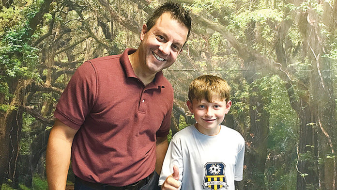 Dr. Mark Bowers and one of his patients, Connor, 9, pose in front of the forest wall at the Brighton Center for Pediatric Neurodevelopment. Photo contributed by Miranda Keskes.