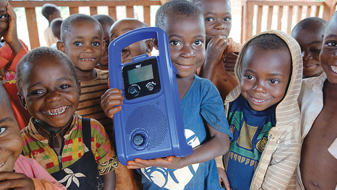 Children in Cameroon hold a crank-powered mp3 player used to deliver preschool lessons to them through the Two Rabbits nonprofit organization. Ann Arbor native Sarah Strader started the organization to help the Baka children of Cameroon find success in a formal classroom setting and their forest home. Photo contributed by Sarah Strader